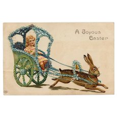 Embossed, antique, Easter postcard of girl in buggy pulled by bunny