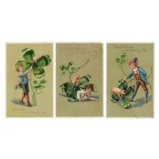 Series of three Tuck St Patrick's Day cards with a boy, a pig and a 4 leaf clover