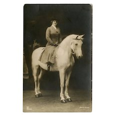 Antique, real photo postcard of silent film star Henny Porten astride a white horse