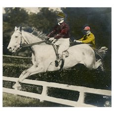 German, undivided back, unposted, hand tinted, real photo postcard of two steeplechase riders clearing a hedge