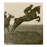 Unposted, European, real photo postcard of two riders jumping a large ditch