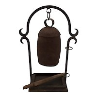 Metal bell on iron stand.