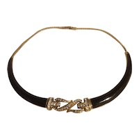 Black and gold tone collar necklace with rhinestone center