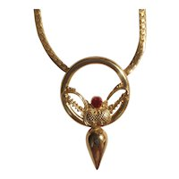 Unique gold tone necklace with a red rhinestone