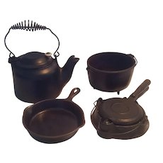 Wagner toy cast iron cookware set including tea kettle, waffle maker, footed pot, and skillet