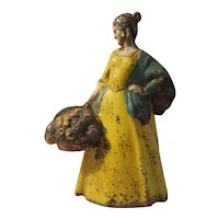 Cast iron doorstop, lady with basket of flowers