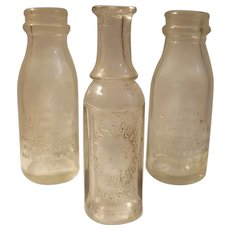 Three small embossed advertising bottles