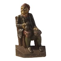 Cast iron doorstop of seated colonial man holding tankard