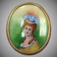 Vintage Brooch with Painted Portrait of a Woman in a Blue and Orange Hat with a Green Background