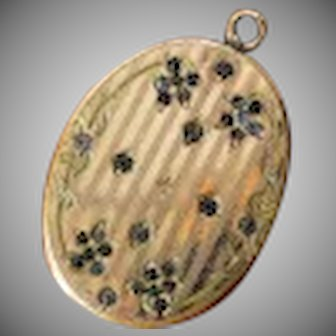 Vintage Art Deco gold tone oval shaped locket with linear engraving and gray rhinestones