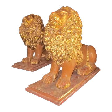 Pair of Painted and Gilt seated Lions on faux marble stands