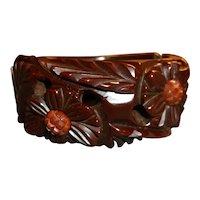 Hinged brown bakelite bangle bracelet with carved flowers