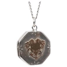 Antique engraved sterling silver locket with a rose motif.
