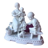 White bisque figurine representing a family playing with a cat