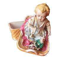 Porcelain toy chest representing a child in a basket with toys