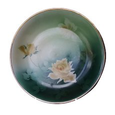 Serving plate with yellow roses with green background.