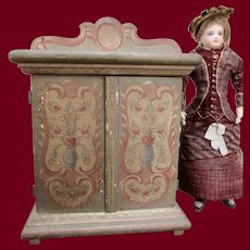 Antique doll armoire of elaborately painted wood.