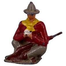 Crescent toy seated lead cowboy with rifle and playing cards