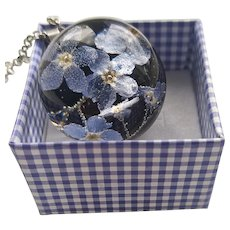 Botanical necklace made of jewelry epoxy resin and forget-me-not flowers.