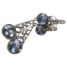 Vintage jewelry: earrings and a ring of blue forget-me-nots on a black background