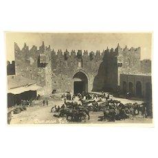 Jerusalem real photo postcard. Busy scene at Damascus Gate with livestock c.1930