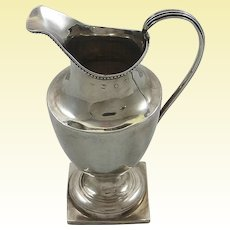 Large George III silver creamer with family crest
