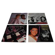 Set of Four 45 RPM Vinyl Records With Picture Sleeves