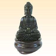 An Ebonized Serpentine Carved Stone Buddha on Stand