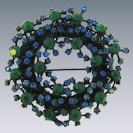 Signed Warner large circular japanned Brooch with blue and green rhinestones