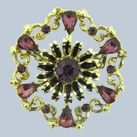 Signed Coro floral circular Brooch with purple rhinestones and black enamel