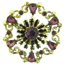 Signed Coro floral circular Brooch with purple rhinestones and black enamel