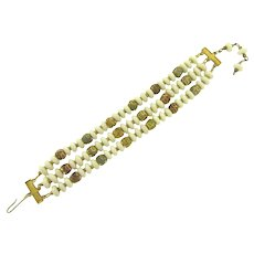 Vintage three strand Bracelet with white glass beads and multicolored filigree capped beads.