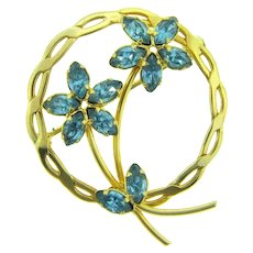 Marked 1/20 12K gold filled circular floral Brooch with blue rhinestones