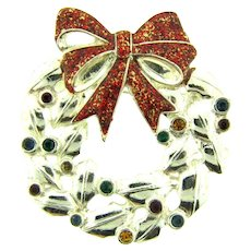 Signed Roman figural Christmas wreath Brooch with rhinestone ornaments and glitter glazed bow