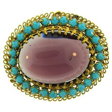 Made in Austria gold tone Brooch with large purple glass cabochon and small blue glass stones