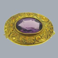 Tiny early Scatter Pin with chased gold tone frame and amethyst glass stone