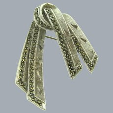 Signed Sphinx  brushed silver tone ribbon Brooch with marcasites
