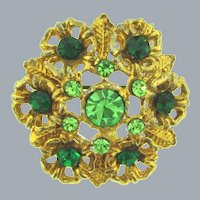 Vintage gold tone circular floral Brooch with green tone rhinestones