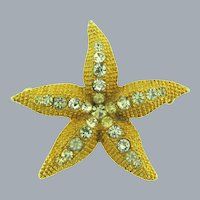 Signed Schrager gold tone figural starfish Brooch with crystal rhinestones