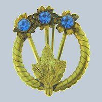 Vintage early circular floral Brooch with blue rhinestones
