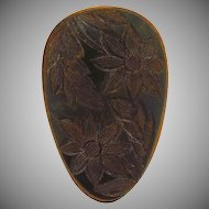 Deeply carved floral dark green Bakelite dress clip