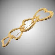 Signed Monet gold tone figural brooch of 4 entwined hearts