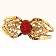 Gold tone clamper Bracelet in a filigree design with oval goldstone center cabochon