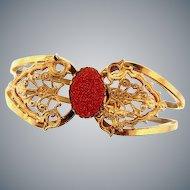 Gold tone clamper Bracelet in a filigree design with oval goldstone center cabochon