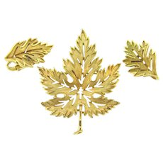Signed Crown Trifari gold tone leaf brooch and matching clip on earrings