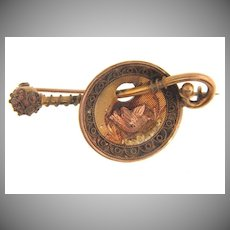 Early vintage Bar Pin with a circular dish depicting a bird with a branch
