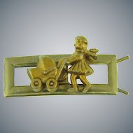 Vintage child's figural barrette of a girl pushing a baby carriage