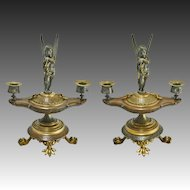 Pair Antique Figural Patinated Bronze Two Light Candelabra / Candlesticks with Winged Cupid on Classical Oil Lamp Shaped Base and Paw Feet - 19th Century, France
