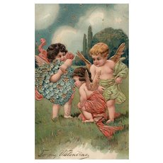 1909 Beautiful Valentine featuring three Cupid angels admiring a Forget me Not Heart PFB Series 8032