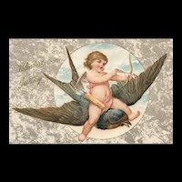 Cupid flying on a blue bird taking a shot with his arrow vintage Valentine postcard John Winsch